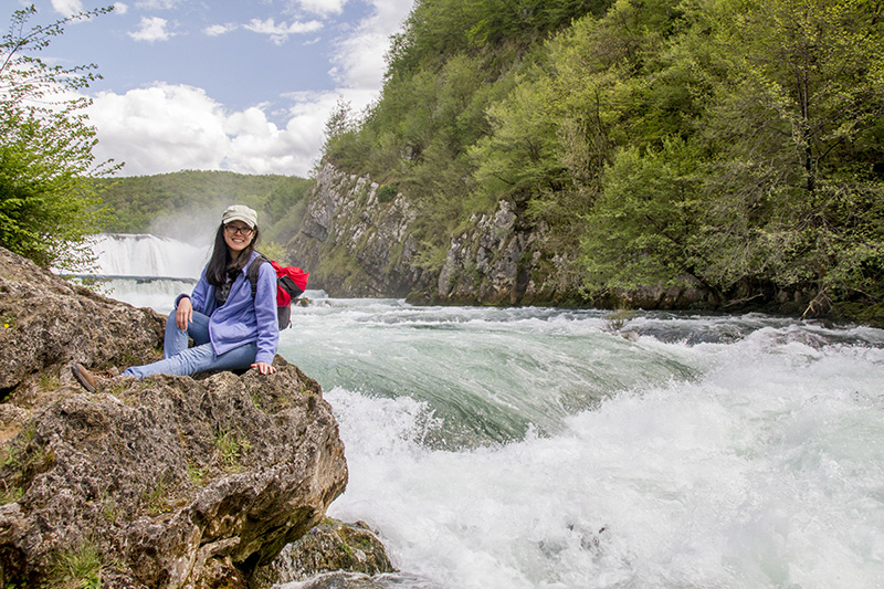 Lin Ying sitting on a huge bounder practically just over the furious river