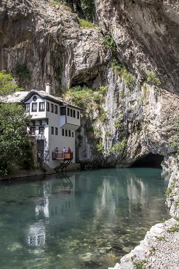 Tekija Blagaj standing below a tall cliff on the edge of the Buna river